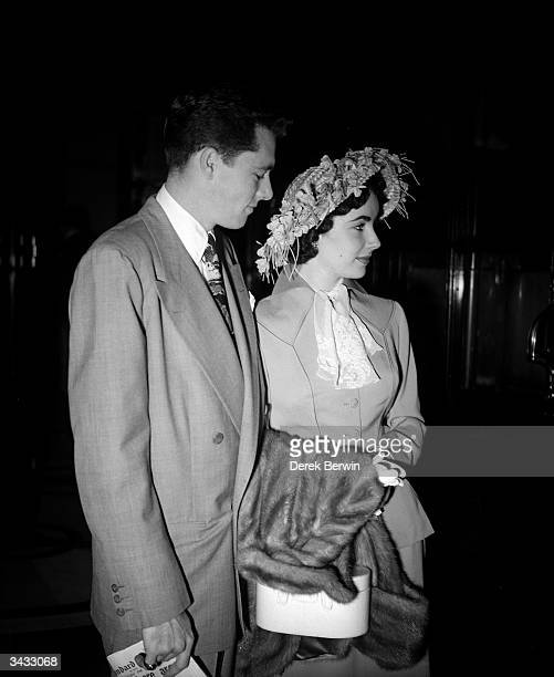 Britishborn film star Elizabeth Taylor and her first husband Conrad 'Nicky' Hilton Jr leaving their London hotel She is wearing a suit of pale blue...