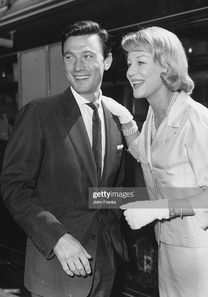 English actress Margaret Leighton (1922 - 1976) greets her husband, Lithuanian born British actor Laurence Harvey (1928 - 1973), at Waterloo, London, on his return from America, where he has been filming in Hollywood. They were divorced in 1961.
