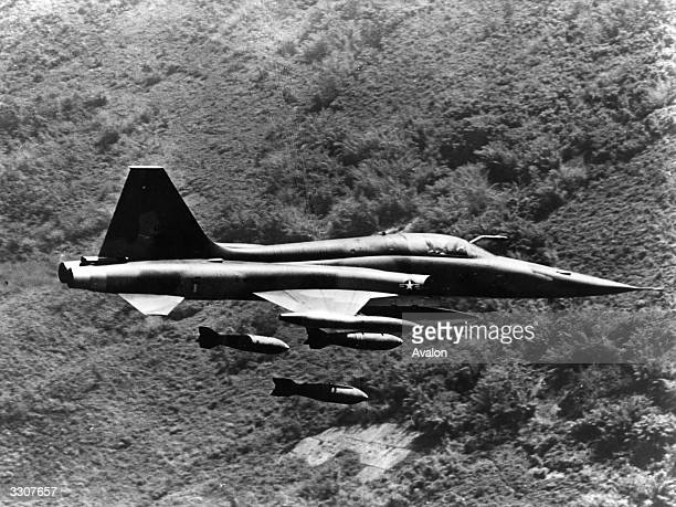 A Northrop F5 Freedom Fighter aeroplane of the US Air Force 4503rd Tactical Fighter Squadron dropping bombs on a Vietcong position over the jungle...