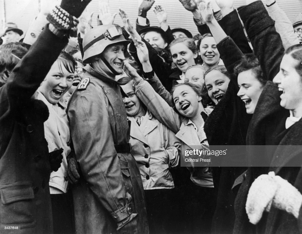 Ecstatic crowds in Salzburg cheer and salute German troops as they enter the city during the Anschluss.