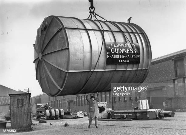 A man guides a 10ton stainless steel fermenting tun constructed in Leven Glasgow as it is hoisted by a crane at Glasgow docks onto the ship...