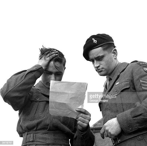 A soldier having difficulty with a letter because he never learned to read at school Original Publication Picture Post 6442 3000 Illiterates Why pub...
