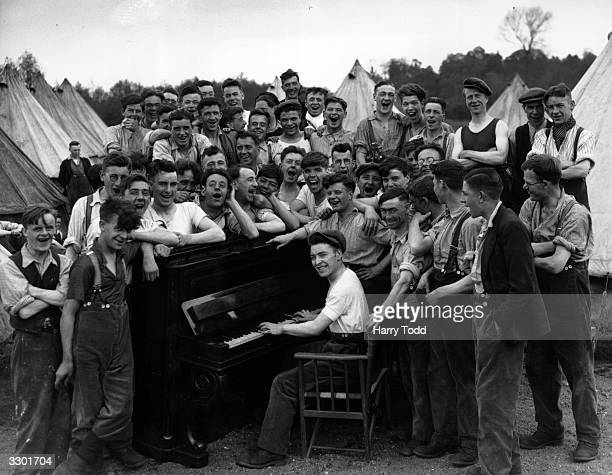 Unemployed men enjoying a singalong around the piano at the Harling Summer Camp which was opened by the Ministry of Labour to provide work in a...