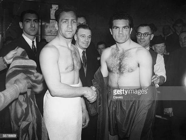 Russian-American boxer Gus Lesnevich shakes hands with Britain's Freddie Mills at the weigh-in for their world light-heavyweight title fight in...