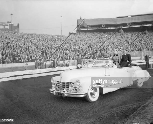American actress Lana Turner travels around the track at Stamford Bridge Stadium during the Midget Car debut