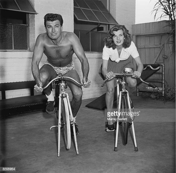 EXCLUSIVE American actor John Bromfield and his wife Frenchborn actor Corinne Calvet sit outside their home exercising on stationary bicycles Los...