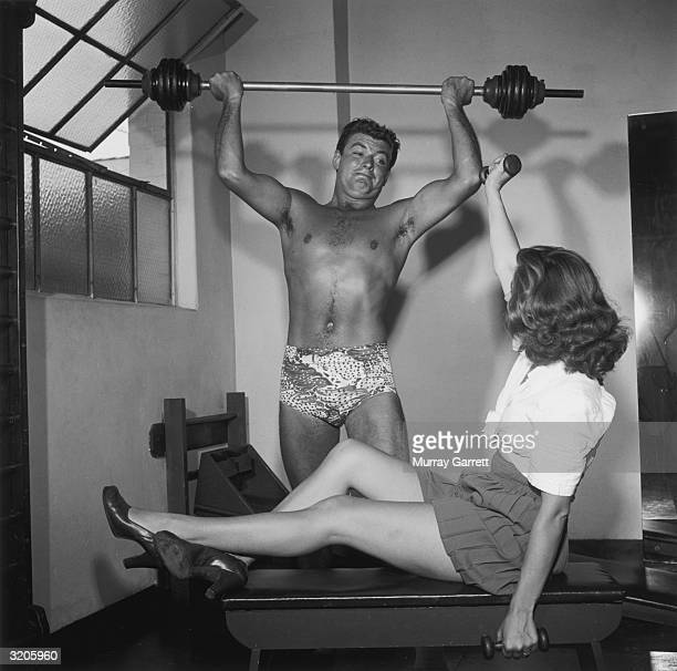 EXCLUSIVE American actor John Bromfield holds a barbell above his head as his wife Frenchborn actor Corinne Calvet sits on a bench lifting dumbbells...
