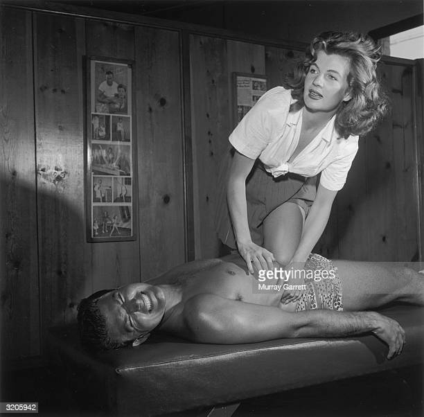 EXCLUSIVE Frenchborn actor Corinne Calvet stands above her husband American actor John Bromfield giving him a massage at their home Los Angeles...