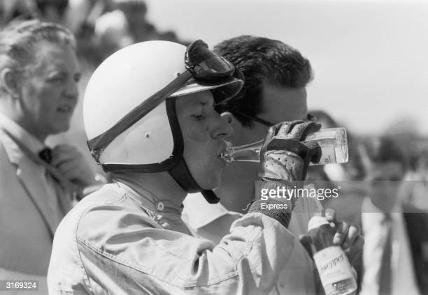 British world champion motorcyclist and racing driver John Surtees drinking from a Schweppes bottle between races at Silverstone
