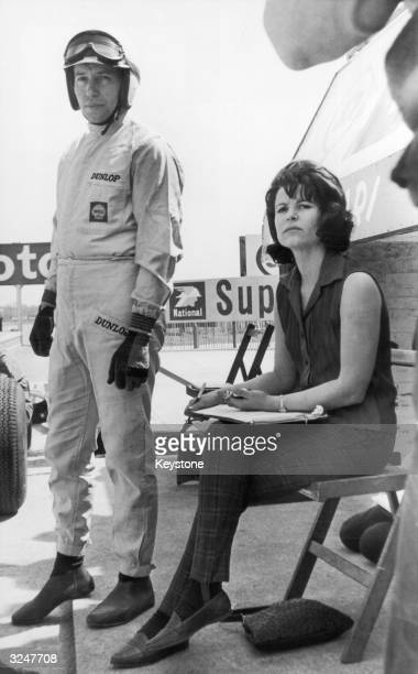 English racing driver John Surtees in the pits at Silverstone with his wife Pat who will be timing his practice laps