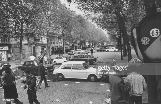 People wandering through a Parisian Boulevard strewn with debris after student riots in Paris