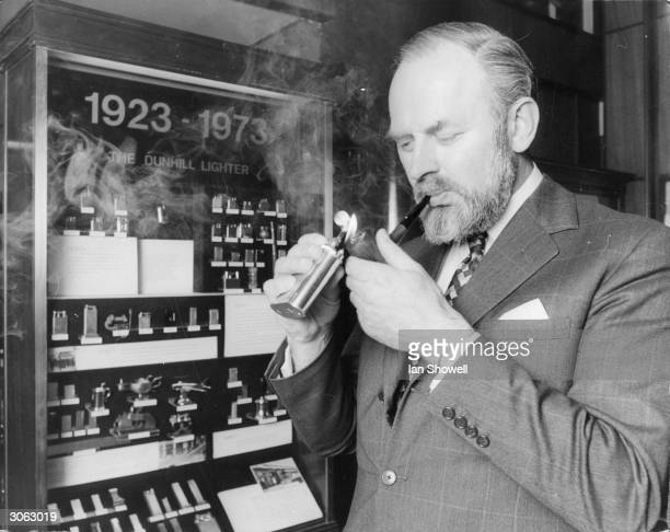 Richard Dunhill Deputy Chairman of Dunhill's and grandson of the founder lighting his pipe at a display tracing the development of the Dunhill lighter