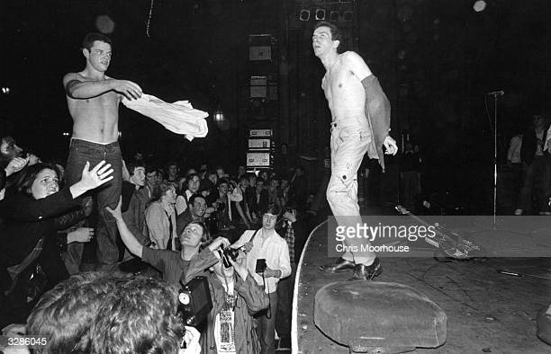 Joe Strummer , lead singer of punk rock band The Clash, exchanges shirts with a fan during a Clash concert at The Rainbow, London.