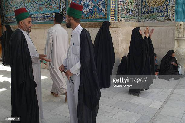 Two guardians stand talking while women in black chador pray at the entrance of the Holy Shrine in Najaf, Iraq. The US forces invaded Iraq to topple...