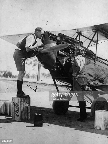 English aviator Amy Johnson and flight lieutenant H C Owen examine her aeroplane 'Jason' after Johnson's arrival in Australia following her solo...