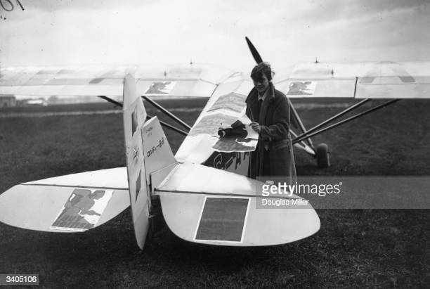 Amy Johnson placing Buy British campaign posters on her plane at Stag Lane Aerodrome London A pioneer aviator she flew solo from England to Australia...