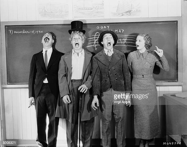The Marx Brothers Harpo Groucho and Chico sing at the top of their voices to the accompaniment of a young woman