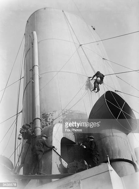 Workmen clean the funnels of the Canadian Pacific liner 'Empress of Britain'