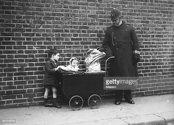 A London policeman looks after some children in Bethnal Green while their mother votes in the General Election