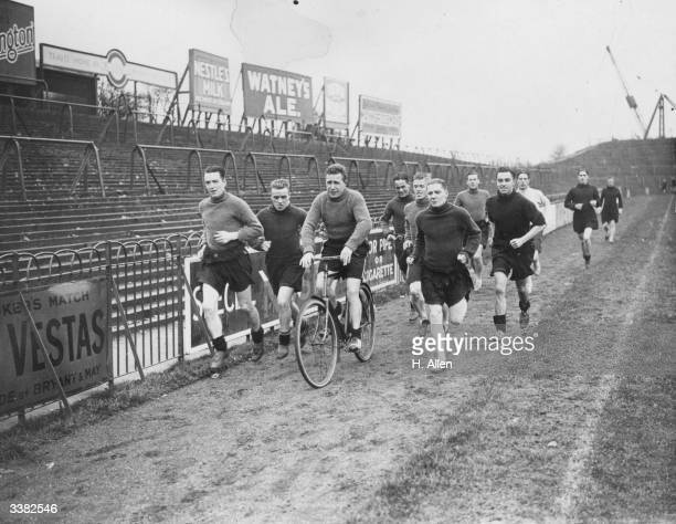 International footballer and cricketer John Arnold of Fulham Football Club and Hampshire County Cricket Club rides his bicycle whilst others run...