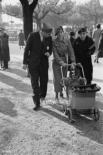 Mother and father both wearing nationalist uniforms take their baby for a ride in her pram accompanied by grandma in San Sebastian which is...