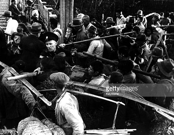 A Shanghai Muncipal Police Officer uses his baton to control the Chinese refugees streaming into the internment settlement during the SinoJapanese war