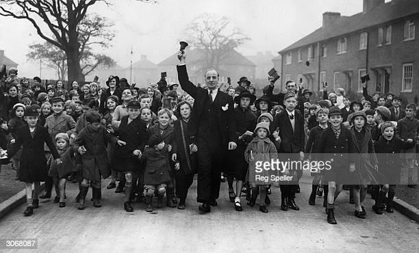 Mr W G Leacha Sunday school teacher rounds up children on an LCC estate at Mottingham for Sunday school class
