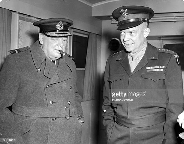 British prime minister Winston Churchill smokes a cigar and listens while General Dwight D Eisenhower Supreme Allied Commander shows him his trailer...
