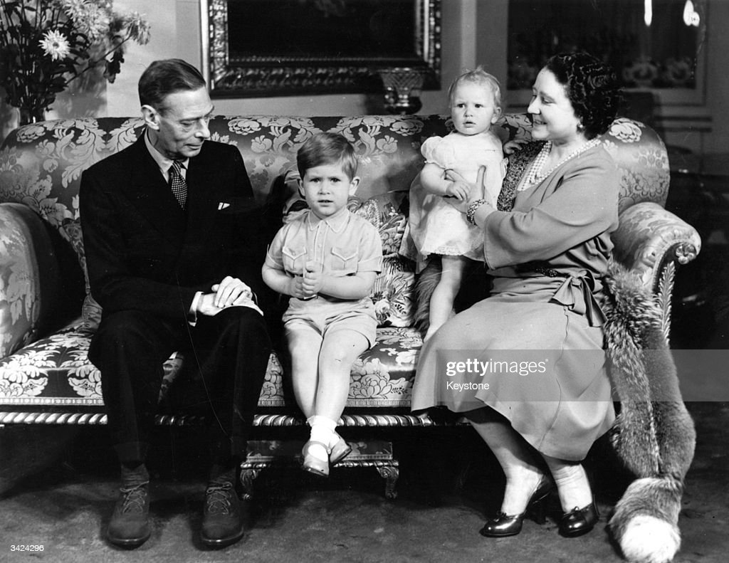 King George VI (1895 - 1952) and Queen Elizabeth (1900 - 2002) in Buckingham Palace with Prince Charles and Princess Anne on the Prince's third birthday.