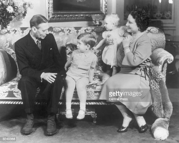 King George VI with Queen Elizabeth and their grandchildren Prince Charles and Princess Anne at Buckingham Palace for Charles' third birthday party...