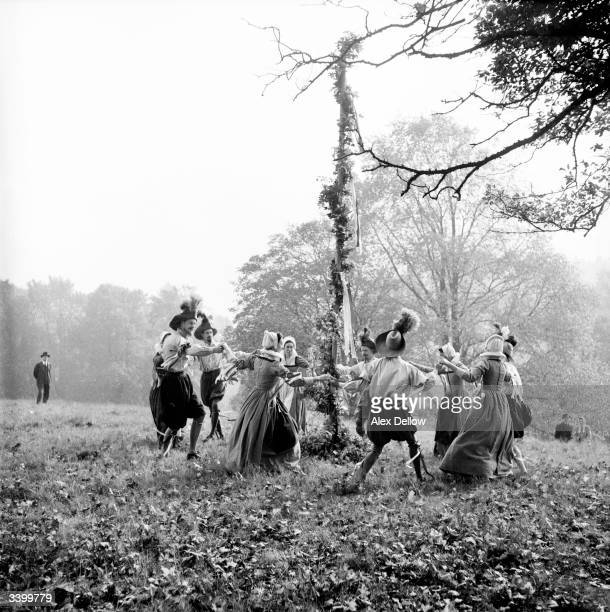 A group of actors in 1596style costumes dance merrily round a maypole during the filming of an Elizabethan television programme in London Original...