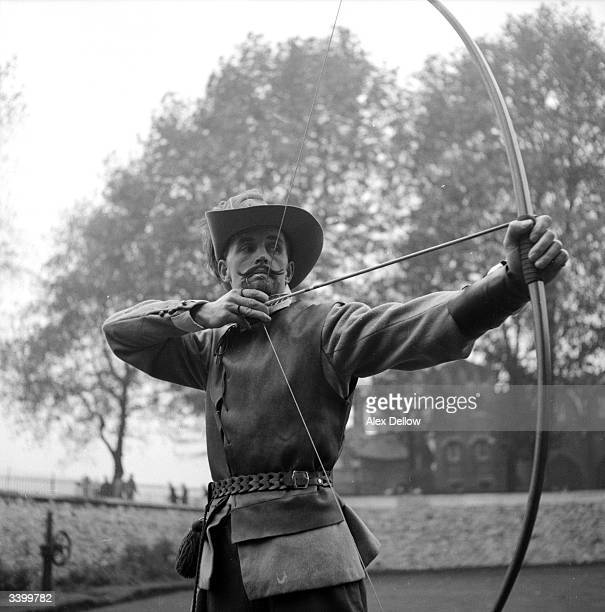 An actor in a 1596style costume draws his bow during the filming of an Elizabethan television programme in London Original Publication Picture Post...