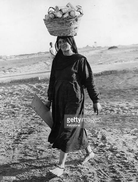 An Egyption woman carrying a basket of tinned fruit she has found on a food dump on the outskirts of Port Said.