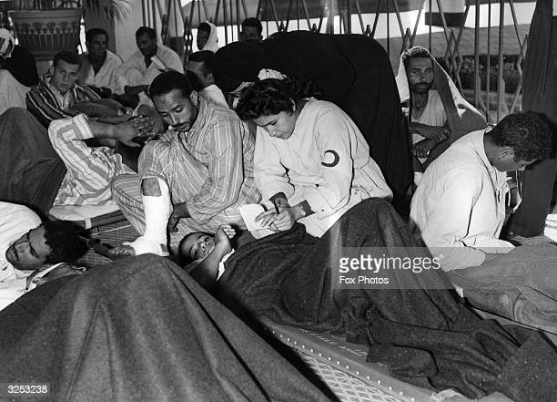 Nurse tends to wounded Egyptians waiting for a train from Port Said to Cairo.