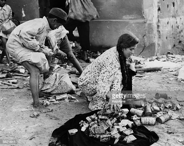 Egyptians searching for food in a food dump on the outskirts of Port Said, Egypt, during the Suez Crisis.