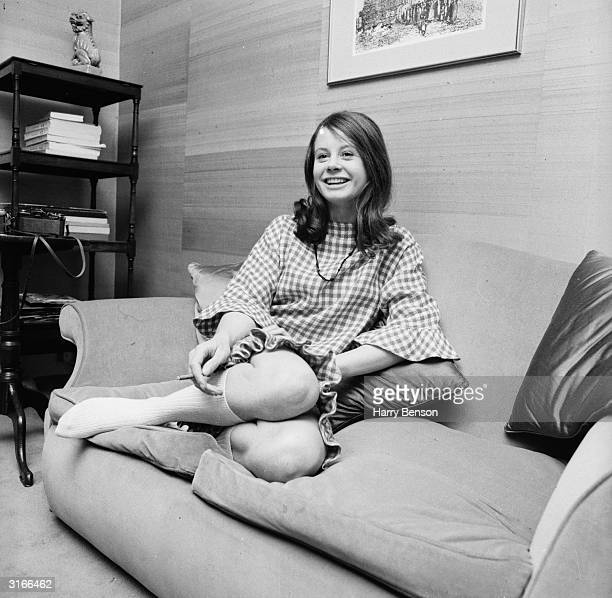 English actress Sarah Miles relaxing on her sofa at home