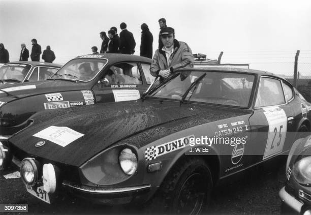 Motor racing driver Tony Fall standing next to his Datsun 240 Z before the start of the 2300 mile RAC International Rally of Great Britain sponsored...