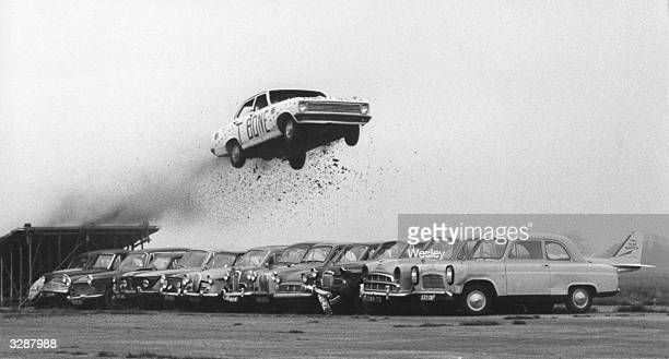 Stunt driver Keith 'TBone' Bowen jumps thirteen parked cars at Thruxton Racecourse near Andover and breaks the world record