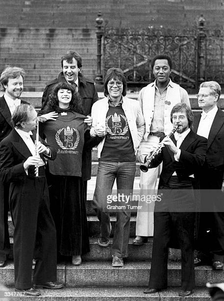 Singers and musicians Kate Bush, Cliff Richard and Labi Siffre pose with Ron Goodwin and members of the London Symphony Orchestra on the steps of the...