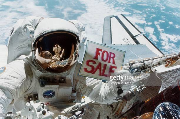 Astronaut Dale A Gardner holding up a for sale sign as a joke during work on the stranded Westar VI satellite Dr Joseph P Allen IV is reflected in...