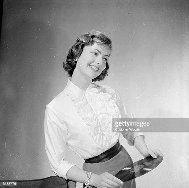 A 50s music lover wearing a ruched blouse tucked inside a pencil skirt