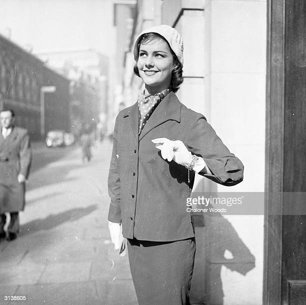 Determined young woman sets out for the day wearing a loose-fitting jacket and matching pencil skirt. Woman's Own