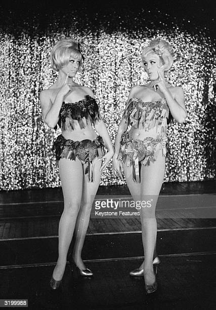 Janet Mahoney and Angela Bracewell dressed in bikinis decorated with party political rosettes during the run up to the 1964 general election