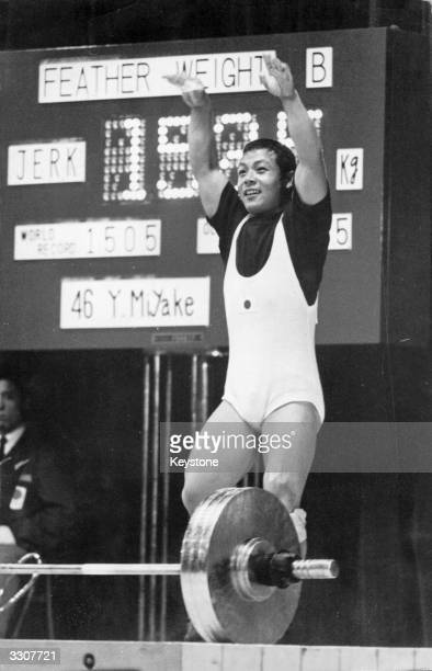 Yoshinobu Miyake of Japan raises his hands in victory after winning a gold medal in the featherweight weightlifting event at the 1964 Tokyo Olympics