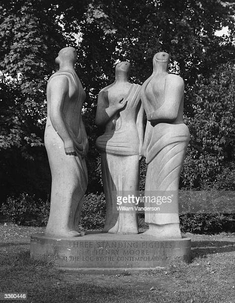 British sculptor Henry Moore's statue of 'Three Standing Figures' by the lakeside at Battersea Park London