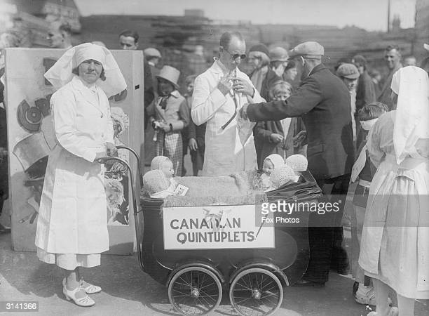 Accompanied by a doctor a nurse is pushing a pram in which are five dolls in the Barking carnival in Essex A notice on the pram says 'Canadian...