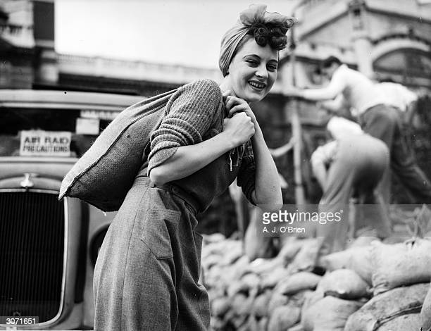 An obliging volunteer from the artists' quarter helps to fill the sandbags which will fortify London's buildings during World War II.