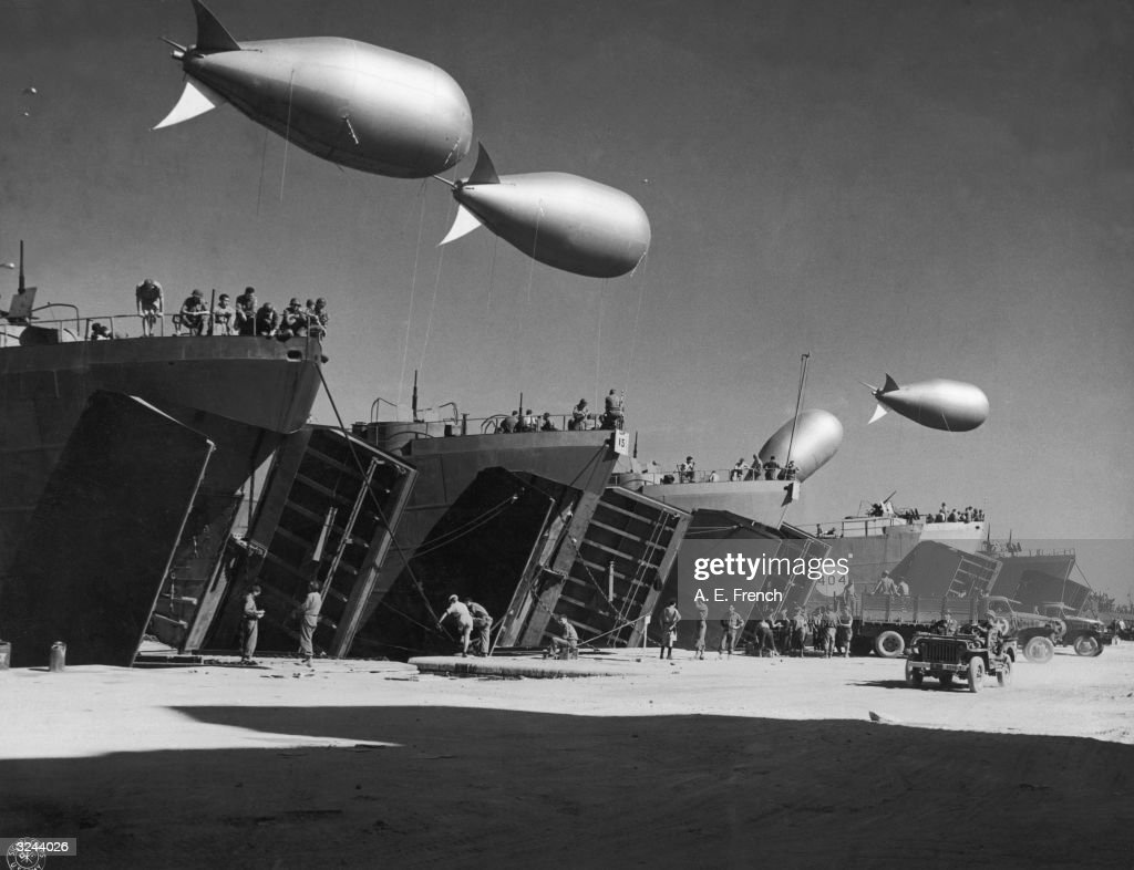 LST boats are loaded with troops and equipment as the US prepares to invade the docks of Palermo, Sicily, Italy. Barrage balloons were used to form a protective covering against the flight paths of enemy aircraft. Ground vehicles move below as troops work to load the ships.