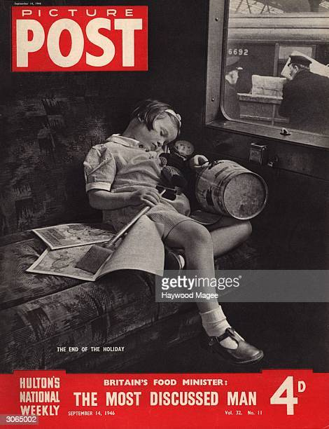 A little girl curls up on the train seat at the end of a seaside holiday clutching her bucket and spade her comics and a rag doll The headline...