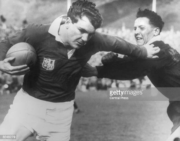 Irish winger Tony O'Reilly of the Lions fends off D J Davison of the Junior All Blacks in a match at Wellington